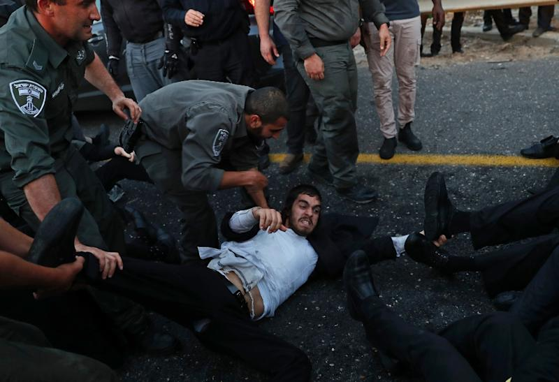 Israeli police remove ultra-Orthodox Jewish demonstrators who blocked a road during a protest against Israeli army conscription in Bnei Brak, near Tel Aviv, on March 12, 2018