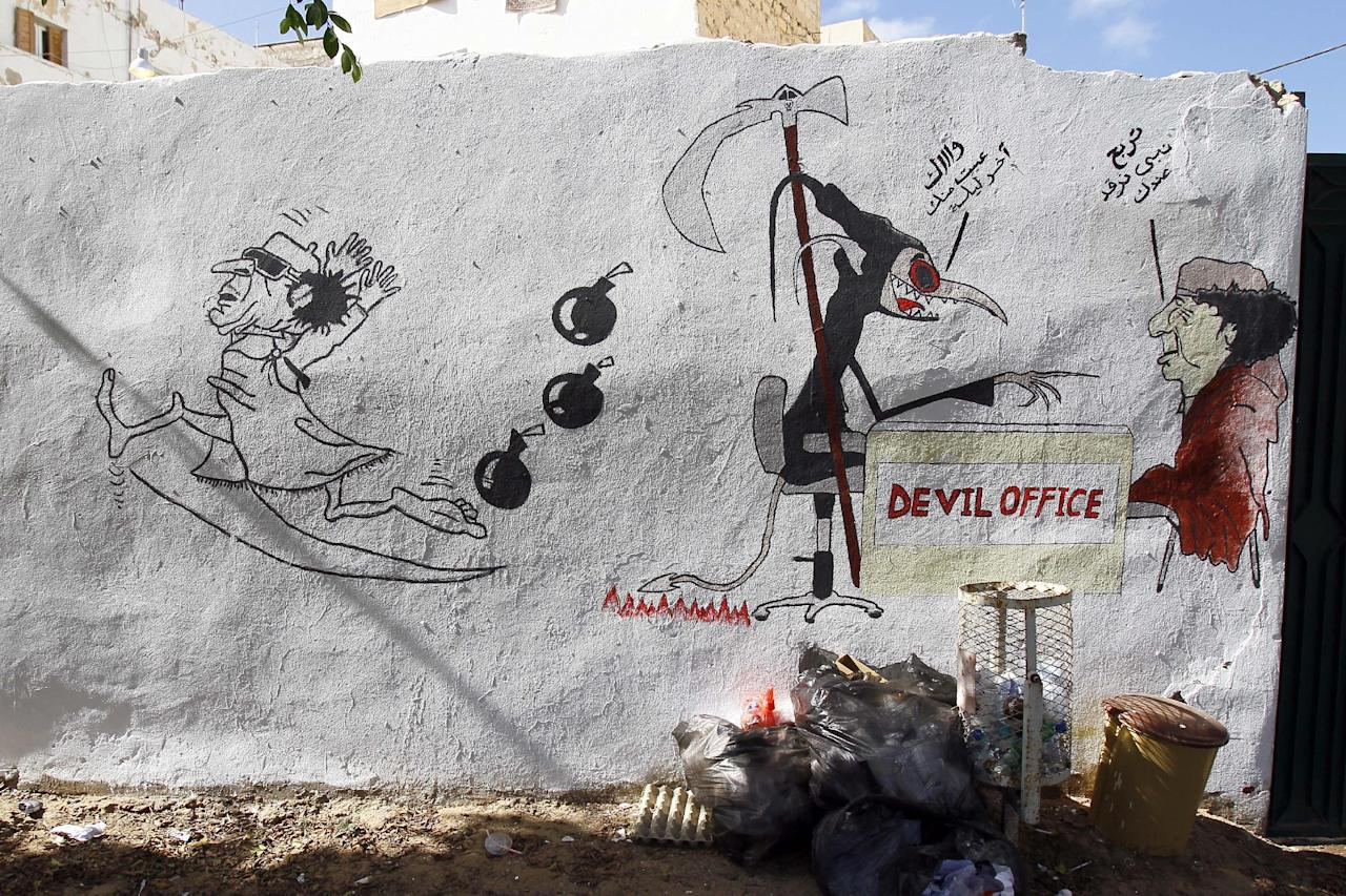 """A graffiti of Libya ousted Moammar Gadhafi saying to the Devil in arabic : Please, Can I Sleep At Your Place"""" as Devil answers """"I Am Fed Up With You This Is Your Last Night"""" is seen on the streets of Tripoli, Libya, Tuesday, Sept. 20, 2011. Libyan graffiti artists are taking advantage of newfound freedom to make fun of ousted leader Moammar Gadhafi on the streets of Tripoli, after 42-years of authoritarian rule artists are now able to express themselves in open public spaces.(AP Photo/Francois Mori)"""