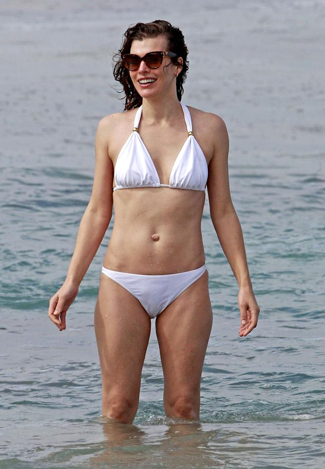 **EXCLUSIVE** 'Resident Evil' babe Milla Jovovich shows her beach ready body in Maui, playing in the surf with her husband Paul Anderson and their daughter Ever