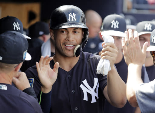 FILE - In this March 2, 2018, file photo, New York Yankees' Giancarlo Stanton is congratulated after scoring on a single by Didi Gregorius during the fifth inning of a the team's baseball spring training game against the Atlanta Braves in Tampa, Fla. After last season the Yankees added the mightiest slugger in the major leagues, Stanton. (AP Photo/Lynne Sladky, File)