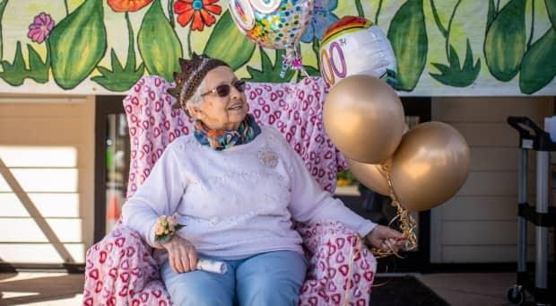 Charlotte Mary England celebrates her 100th birthday with family members and friends during a drive-by celebration at her residence at Augustine House Society in Delta, British Columbia on Monday, April 19, 2021.