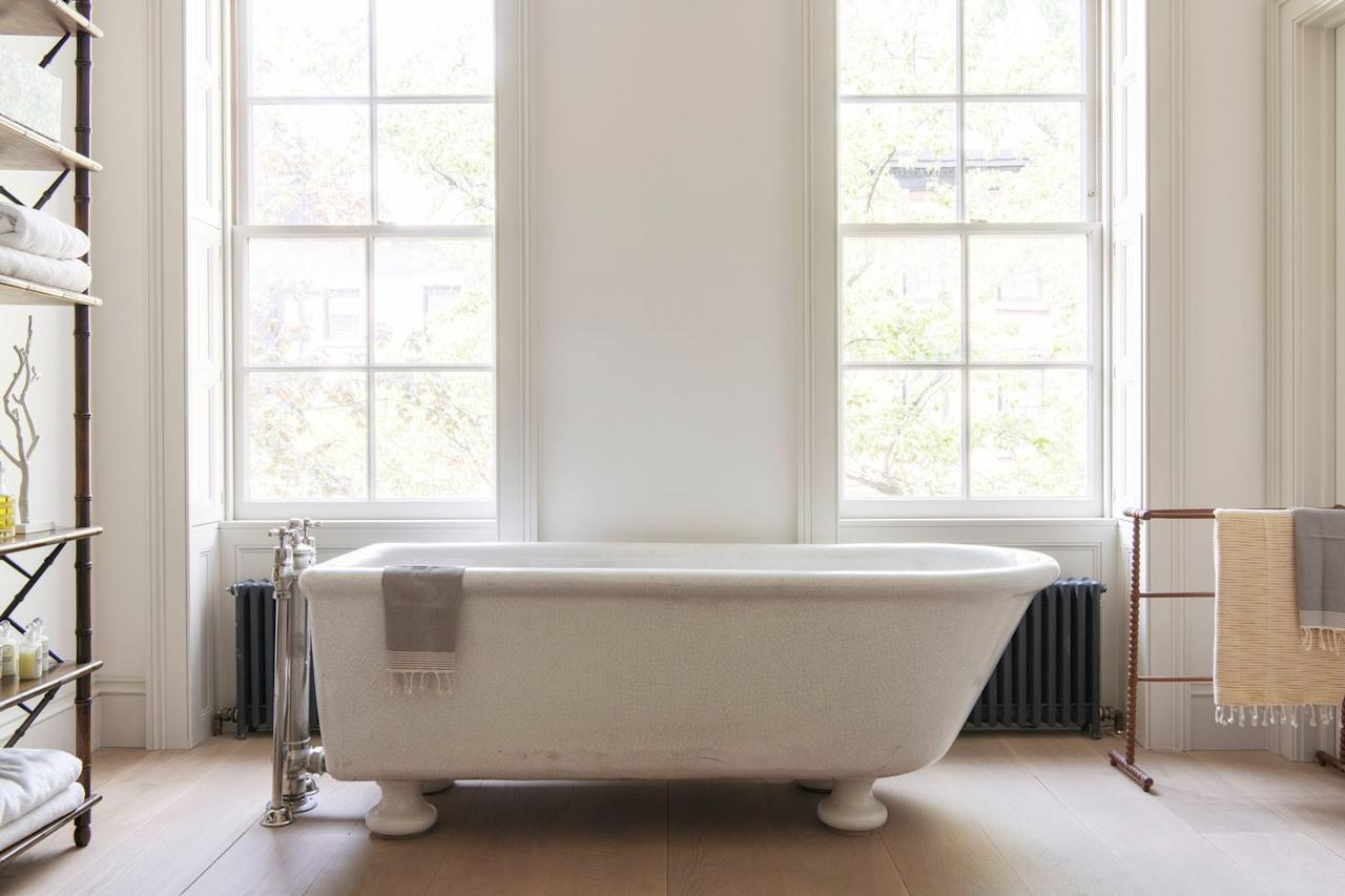 """<p>In this bathroom designed by <a href=""""https://www.elizabethroberts.com/"""" target=""""_blank"""">Elizabeth Roberts Architecture & Design</a>, the radiator takes up a pretty big portion of the wall. The bathroom is then strategically laid out to cover most of it with a horizontal bathtub. And instead of painting it white in order to have it blend in with the fall, it's a moody gray hue that's accented by thew Turkish towel. </p>"""