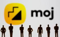 Small toy figures are seen in front of displayed Moj logo in this illustration taken