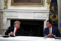 President Donald Trump laughs with Oklahoma Gov. Kevin Stitt during a roundtable with governors on the reopening of America's small businesses, in the State Dining Room of the White House, Thursday, June 18, 2020, in Washington. (AP Photo/Alex Brandon)