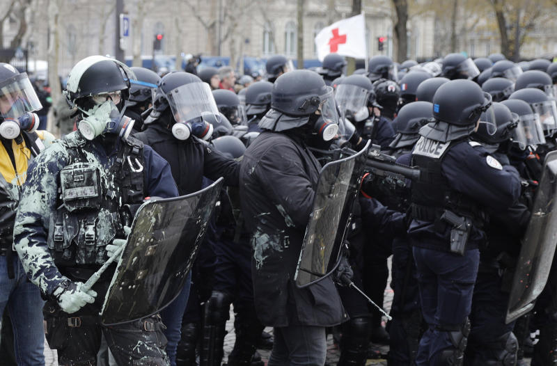 FILE - In this Saturday, Jan. 12, 2019 file photo riot police take position during clashes yellow vest protesters clash around the Arc of Triomphe in Paris, France. (AP Photo/Kamil Zihnioglu, File)