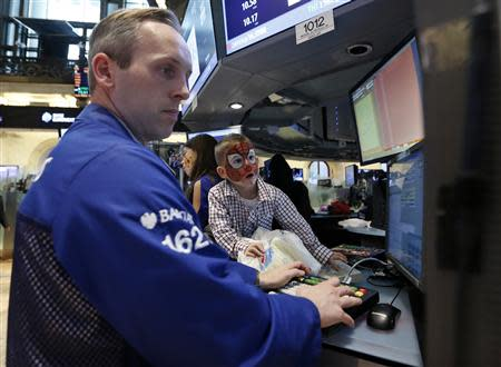 A trader monitors trades as a young boy watches on the floor of the New York Stock Exchange