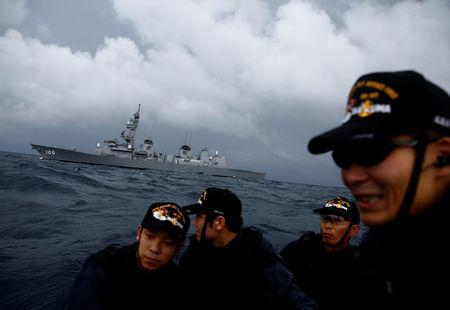 Japanese destroyer Inazuma is seen behind one of its ship inspection teams on a small patrol boat in the Indian Ocean