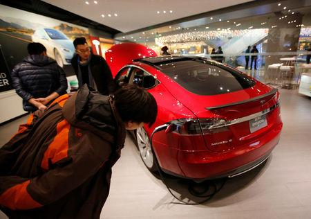 FILE PHOTO: Visitors look at a Tesla Model S car at a Tesla showroom in Beijing