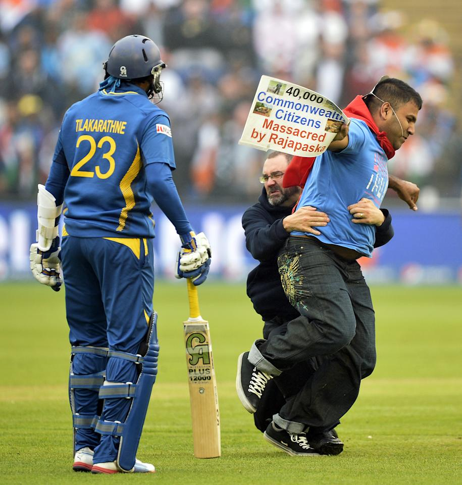 Sri Lanka's Tillakaratne Dilshan (L) looks on as a groundsman tackles a demonstrator who ran onto the pitch during the 2013 ICC Champions Trophy semi-final cricket match between India and Sri Lanka at the Cardiff Wales stadium in Cardiff on June 20, 2013. AFP PHOTO/ADRIAN DENNIS --  RESTRICTED TO EDITORIAL USE --