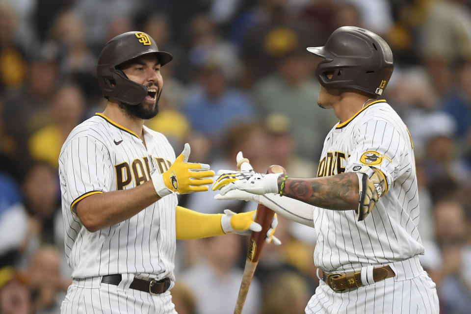 San Diego Padres' Manny Machado (13), right, is congratulated by Eric Hosmer (30) after hitting a solo home run during the first inning of a baseball game against the Los Angeles Dodgers Wednesday, June 23, 2021, in San Diego. (AP Photo/Denis Poroy)