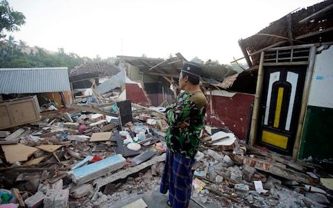 A man inspects the ruin of his house destroyed by an earthquake in North Lombok, Indonesia - Credit: Firdia Lisnawati/ AP