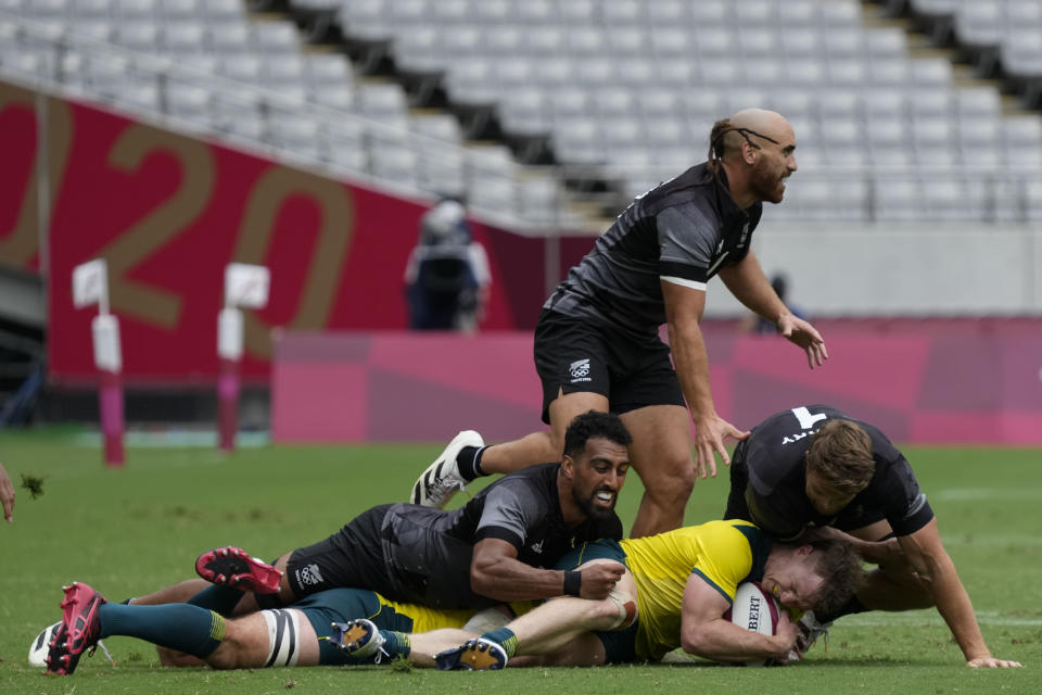 CORRECTS NAME TO HENRY HUTCHISON FROM NICK MALOUF - Australia's Henry Hutchison clings to the ball under pressure from New Zealand's Amanaki Nicole, left, and Scott Curry, right, in their men's rugby sevens match at the 2020 Summer Olympics, Tuesday, July 27, 2021 in Tokyo, Japan. (AP Photo/Shuji Kajiyama)