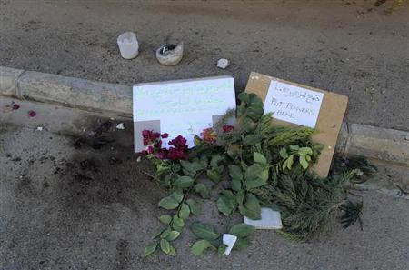 Notes, flowers and candles placed by people at the scene where American teacher Ronnie Smith was shot dead are seen in Benghazi
