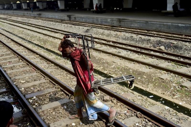 A Bangladeshi railway porter carries a trolley at a Railway Station in Dhaka on February 24, 2015, during an on-going nationwide strike and blockade of the Bangladesh Nationalist Party office (AFP Photo/Munir Uz Zaman)