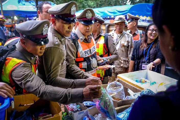 <p>A group of police officers takes supplies provided by volunteers near Tham Luang Nang Non Cave on June 29, 2018, in Chiang Rai, Thailand, during the search for 12 boys and their soccer coach. (Photo: Linh Pham/Getty Images) </p>