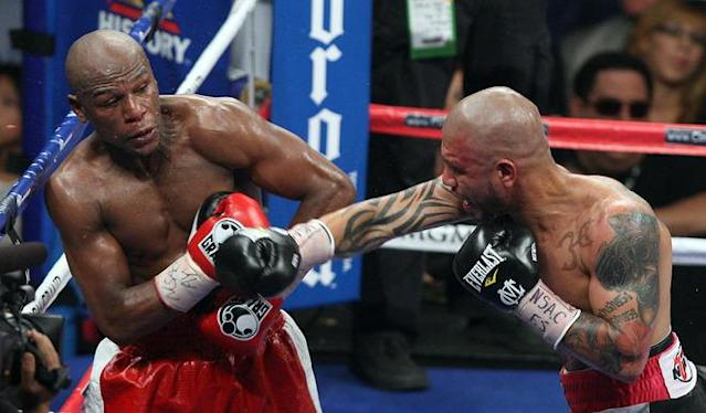 Floyd Mayweather (L) backs away from a right from Miguel Cotto during of their WBA super welterweight title fight at the MGM Grand in Las Vegas on May 5, 2012. Mayweather won the WBA super welterweight title in a 12-round unanimous decision. AFP PHOTO/John GurzinskiJOHN GURZINSKI/AFP/GettyImages