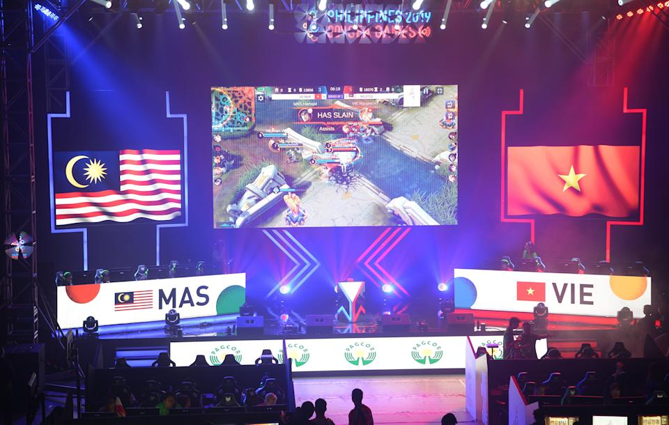 TOPSHOT - Gamers from Malaysia (L) and Vietnam (R) compete in the qualifying rounds of the eSports event at the SEA Games (Southeast Asian Games) in Manila on December 5, 2019. (Photo by TED ALJIBE / AFP) (Photo by TED ALJIBE/AFP via Getty Images)
