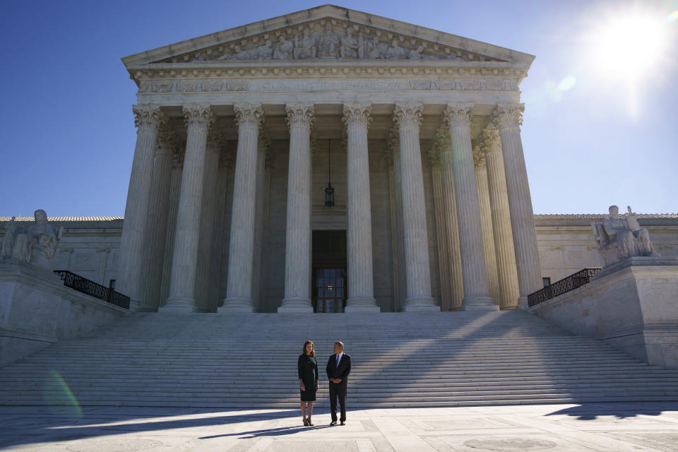 Associate Justice Amy Coney Barrett, left, is escorted for a traditional investiture ceremony by Chief Justice of the United States John Roberts, at the Supreme Court in Washington, Friday, Oct. 1, 2021. Barrett, appointed by President Donald Trump, took her place on the high court in October 2020, but the COVID-19 pandemic delayed the ceremony. (AP Photo/J. Scott Applewhite)