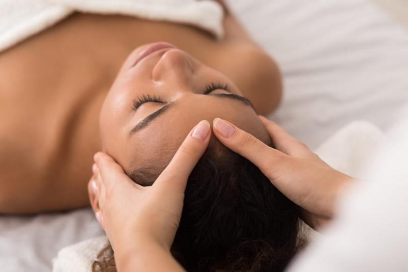woman receiving a massage and facial