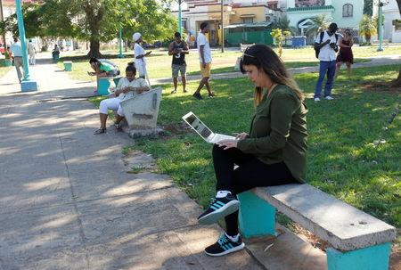 Elaine Diaz, who founded web-based outlet Periodismo de Barrio in 2015, connects to the internet at a hotspot at a park, in Havana, Cuba February 5, 2018. REUTERS/Stringer