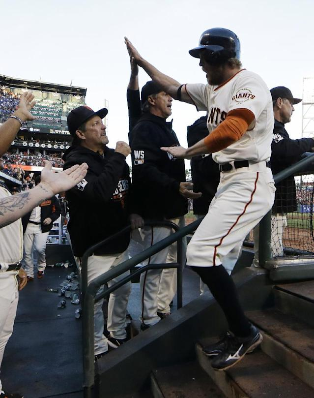 San Francisco Giants Hunter Pence is congratulated by teammates after scoring on an RBI ground out by Brandon Crawford during the second inning of Game 5 of baseball's World Series against the Kansas City Royals Sunday, Oct. 26, 2014, in San Francisco. (AP Photo/David J. Phillip)