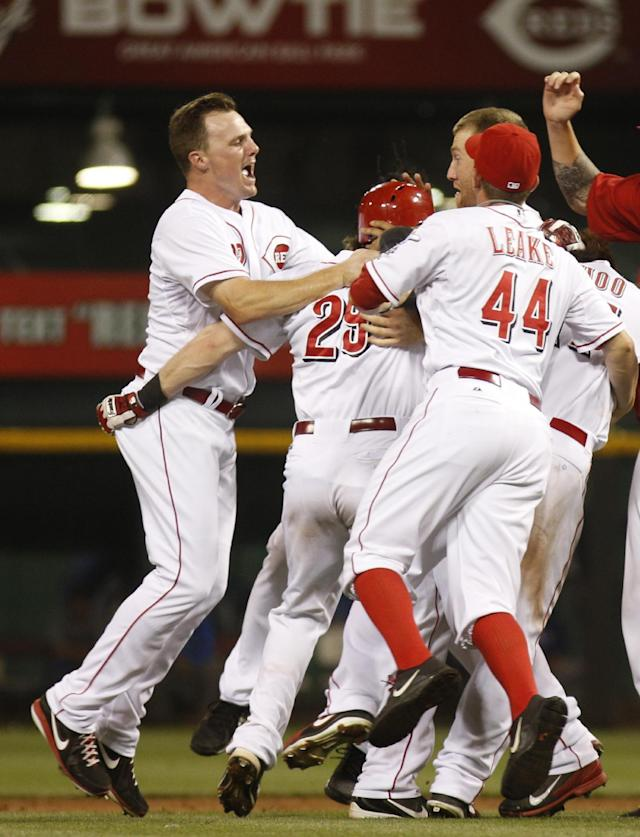 Cincinnati Reds' Jay Bruce, left, and Mike Leake, right, celebrate with Ryan Hanigan, middle, after Hanigan hit an RBI game-winning double off Los Angeles Dodgers relief pitcher Ronald Belisario in the ninth inning during a baseball game, Sunday, Sept. 8, 2013, in Cincinnati. The Reds won 3-2. (AP Photo/David Kohl)