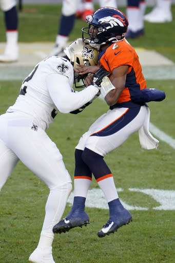 Denver Broncos quarterback Kendall Hinton (2) is hit after the throw by New Orleans Saints defensive end Marcus Davenport during the first half of an NFL football game, Sunday, Nov. 29, 2020, in Denver. (AP Photo/David Zalubowski)