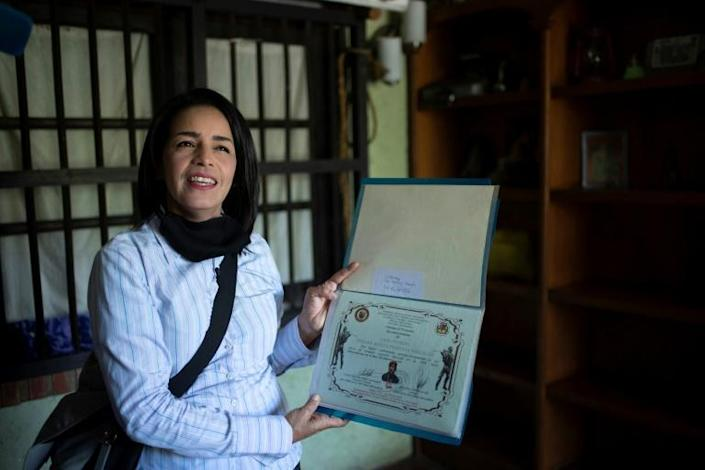 """Ismaira Figueroa, a sniper for the Bolivarian militia in Venezuela, keeps a folder with her diplomas, including a sheet of paper with six holes in it that confirmed her graduation as an """"expert marksman"""" in 2016"""