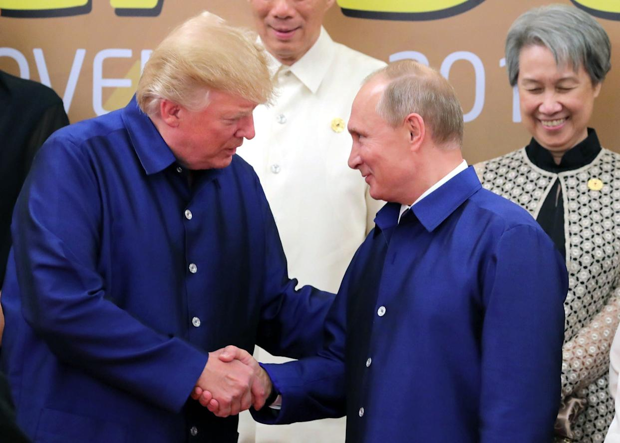 President Donald Trump shakes hands with Russia's President Vladimir Putin (R) as they pose for a group photo ahead of the Asia-Pacific Economic Cooperation (APEC) Summit leaders gala dinner in the central Vietnamese city of Danang on November 10, 2017.