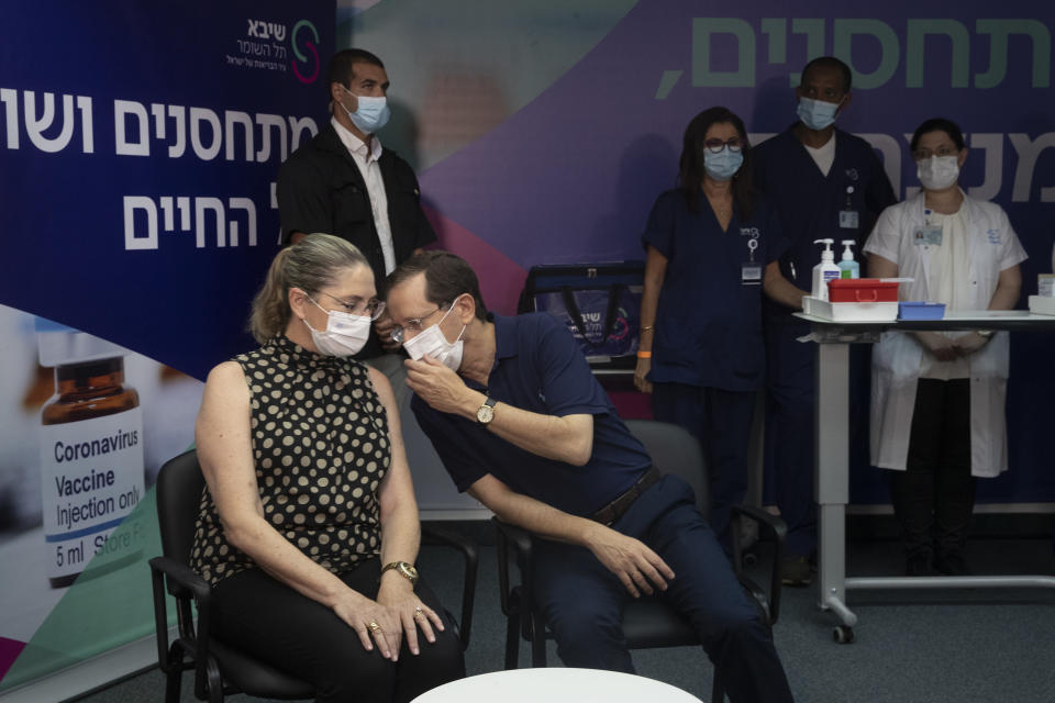 Israeli President Isaac Herzog speaks to his wife, Michal, left, before the couple received a third coronavirus vaccine at the Sheba Medical Center in Ramat Gan, Israel, Friday, July 30, 2021. (AP Photo/Maya Alleruzzo, Pool)