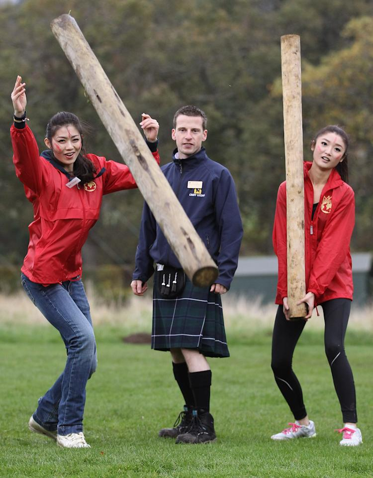 CRIEFF, SCOTLAND - OCTOBER 24:  Chen Liu from China, and Chu Hay Man Hyman from Hong Kong pose with Ross McMillan during the caber tossing at the Miss World Highland Games at Crieff Hotel on October 24, 2011 in Crieff, Scotland. One hundred and twenty two participants of the Miss World are visiting Scotland to as part of a UK tour to celebrate Miss World's 60th birthday. The final of the competition will take place in Earls Court, London on Sunday 6trh of November.  (Photo by Jeff J Mitchell/Getty Images)
