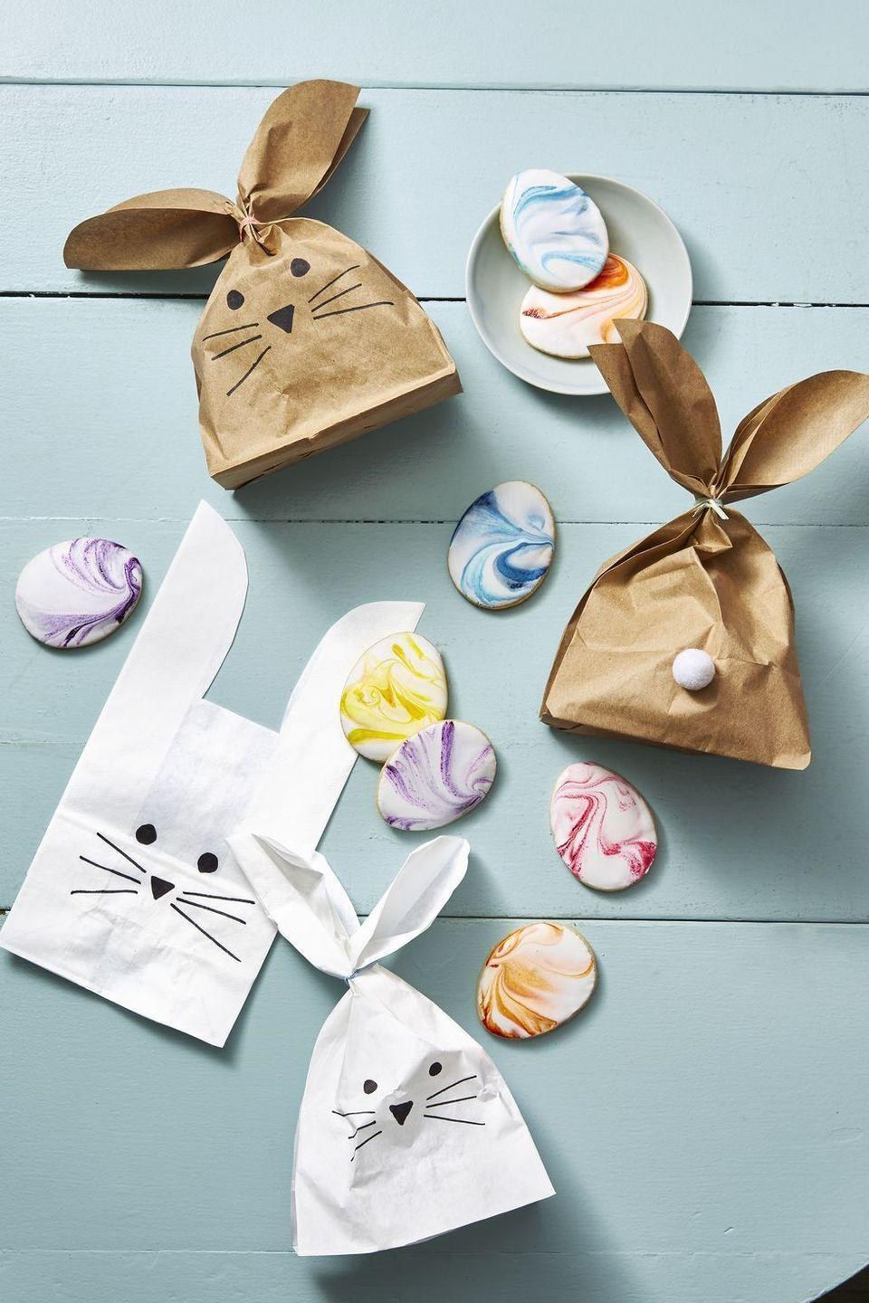 <p>If you're short on storage space, go with something that you can fold up or recycle as soon as the holiday wraps. Cut paper bags to make bunny-ear shapes, then draw on a bunny face with a black marker and finish it off with a pom-pom tail. Fill it with all of their chocolates, candies, and other holiday treats as you would a normal basket! </p>