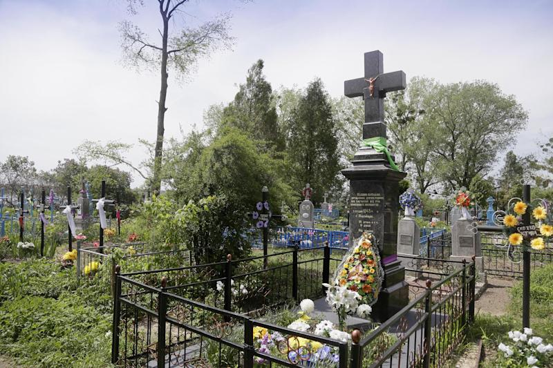 """In this picture taken May 10, 2013, a monument pays tribute to civilians who were burned alive during WWII in Pidhaitsi close to Ukraine's western city of Lutsk. The monument reads: """"To our parents, wives, children, who were murdered by the German occupants on December 3, 1943 in Pidhaitsi. 21 people, including 9 children."""" Evidence uncovered by AP indicates that Ukrainian Self Defense Legion commander Michael Karkoc's unit was in the area at the time of the massacre. (AP Photo/Efrem Lukatsky)"""