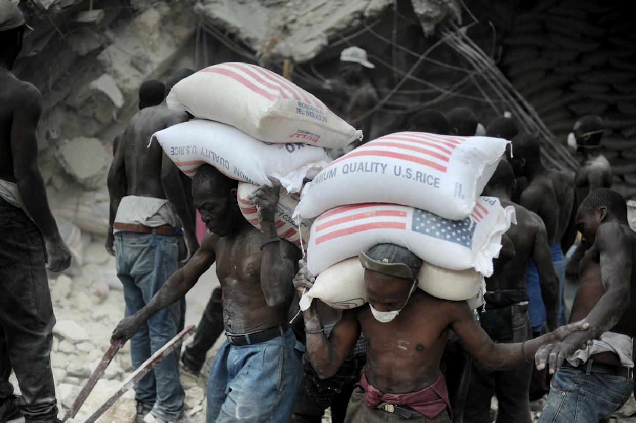 Workers remove rice from a warehouse after the earthquake in Port-au-Prince on Jan. 26, 2010.