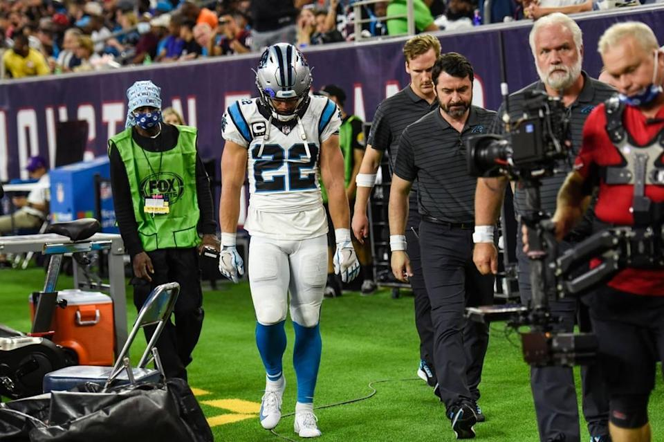 Panthers running back Christian McCaffrey, center, hangs his head as he leaves the medical tent after a hamstring injury during the game against the Texans at NRG Stadium on Thursday, September 21, 2021 in Houston, TX.