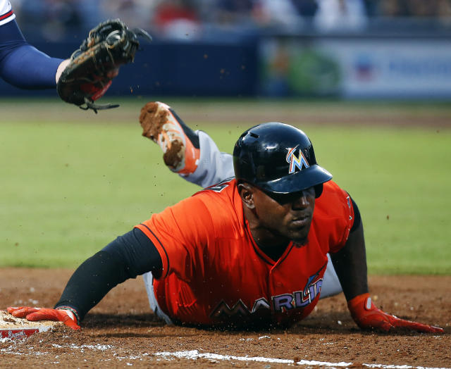 Miami Marlins right fielder Marcell Ozuna slides into first base after being picked off in the third inning of a baseball game against the Atlanta Braves Monday, April 21, 2014 in Atlanta. (AP Photo/John Bazemore)