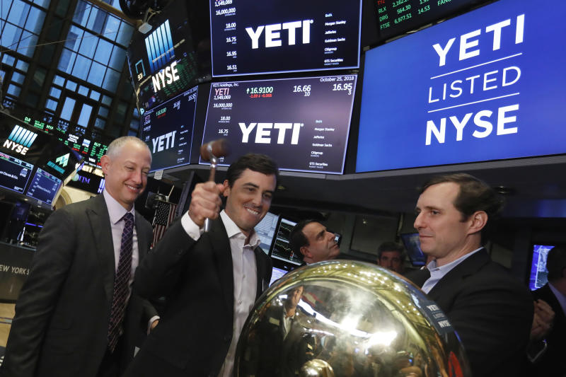 Yeti co-founder Roy Seiders, second left, is flanked by Cortec Managing Partner David Schnadig, left, and Yeti CEO Matt Reintjes, right, as he rings a ceremonial bell when his company's IPO begins trading, on the floor of the New York Stock Exchange, Thursday, Oct. 25, 2018. (AP Photo/Richard Drew)