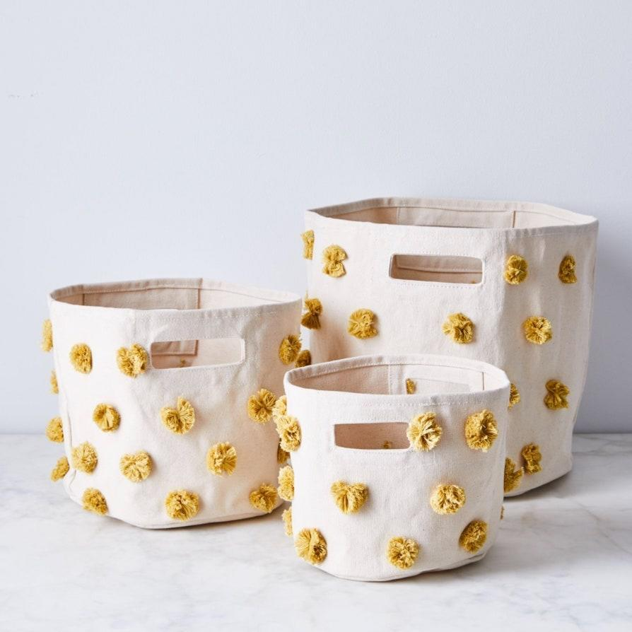"""Times are tough, but at least these yellow pom-poms are a mood boost (also available in blue, gray, and pink). $24, Food52. <a href=""""https://food52.com/shop/products/6350-pom-pom-storage-bins"""" rel=""""nofollow noopener"""" target=""""_blank"""" data-ylk=""""slk:Get it now!"""" class=""""link rapid-noclick-resp"""">Get it now!</a>"""