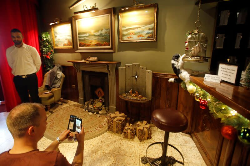 """Man takes pictures of an artwork dubbed """"scar of Bethlehem"""" by street artist Banksy in the Walled Off hotel, in Bethlehem in the Israeli-occupied West Bank"""