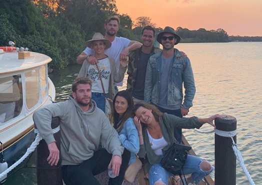 A photo of Liam Hemsworth, Elsa Pataky and Chris Hemsworth and friends posing on a jetty next to a boat.
