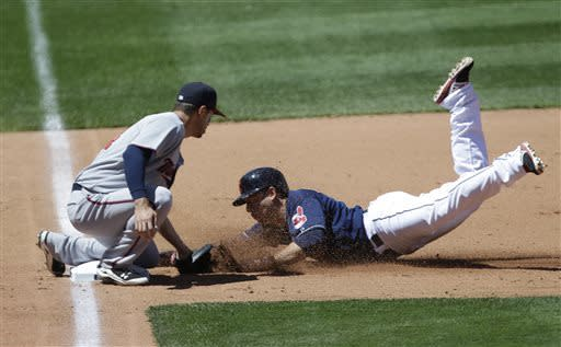 Cleveland Indians' Asdrubal Cabrera, right, steals safely into third base as Minnesota Twins' Trevor Plouffe tries to make the tag in the fourth inning of a baseball game on Sunday, May 5, 2013, in Cleveland. (AP Photo/Tony Dejak)