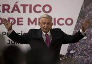 FILE - In this July 1, 2021 file photo, Mexican President Andres Manuel Lopez Obrador waves after giving a speech at a ceremony marking the third anniversary of his presidential election at the National Palace in Mexico City. Mexico's anti-monopoly regulator has on Wednesday, July 28, 2021, openly criticized President Lopez Obrador's plan to set a maximum price for cooking and heating gas. (AP Photo/Fernando Llano, File)