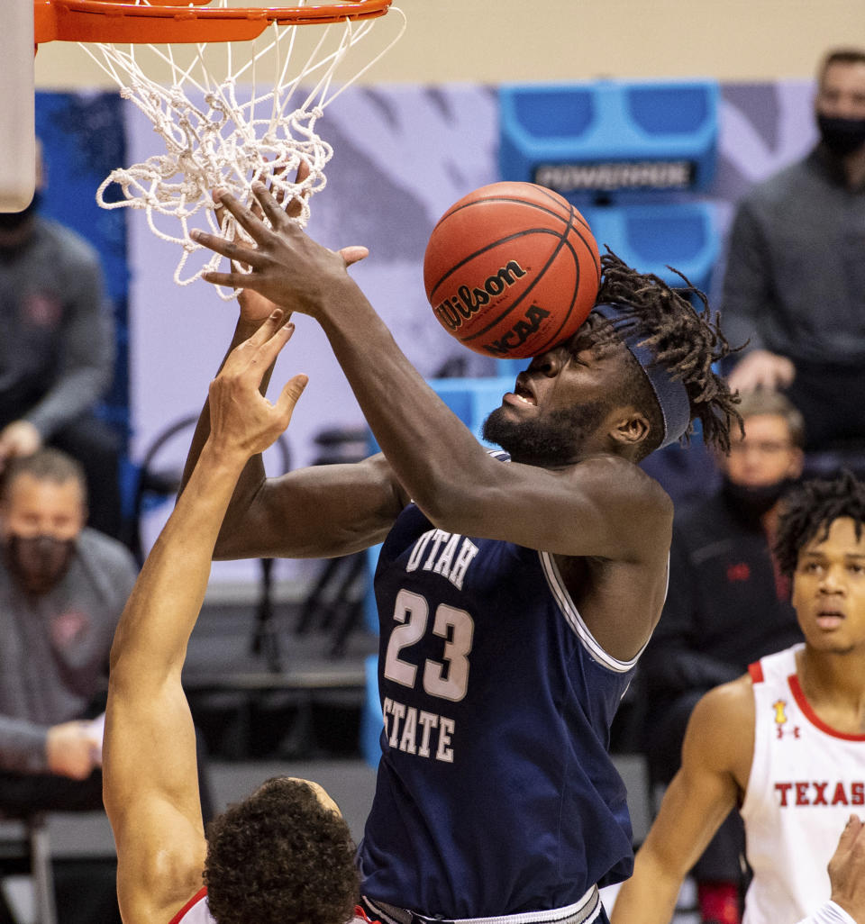 The basketball hits the face of Utah State center Neemias Queta (23) after his layup attempt ricocheted off the rim during the first half of a first round game against Texas Tech in the NCAA men's college basketball tournament, Friday, March 19, 2021, in Bloomington, Ind. (AP Photo/Doug McSchooler)