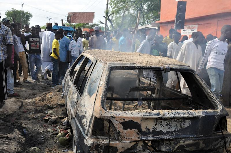 People gather to look at a burnt car following a bomb explosion that rocked the busiest roundabout near the crowded Monday Market in Maiduguri, Borno State, on July 1, 2014