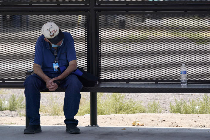 A person waits for a bus in the shade as the heat wave in the Western states continues Thursday, June 17, 2021, in Phoenix. (AP Photo/Ross D. Franklin)