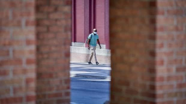 A masked pedestrian walks on O'Connor Street in downtown Ottawa during the COVID-19 pandemic. (David Richard/Radio-Canada - image credit)