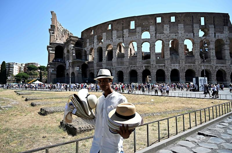 A street vendor sells his hats to tourists in front of the Colosseum in Rome on July 26, 2019 during a heatwave that smashed records across Europe. - The heatwave, which was expected to ease up on July 26, 2019 as rain and thunderstorms move in, again focused public attention on the problems caused by climate change. (Photo by Vincenzo PINTO / AFP) (Photo credit should read VINCENZO PINTO/AFP/Getty Images)