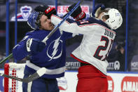 Tampa Bay Lightning's Ryan McDonagh, left, and Columbus Blue Jackets' Josh Dunne engage during the first period of an NHL hockey game Thursday, April 22, 2021, in Tampa, Fla. (AP Photo/Mike Carlson)
