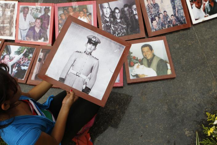 A mourner places a photo of the late President Hugo Chavez when he was a military cadet on a makeshift altar at the main square of Sabaneta, the town of his birth in western Venezuela on Saturday, March 9, 2013. Chavez died of cancer on March 5, 2013. His former house has been turned into the local headquarters of the United Socialist Party of Venezuela, PSUV. (AP Photo/Esteban Felix)