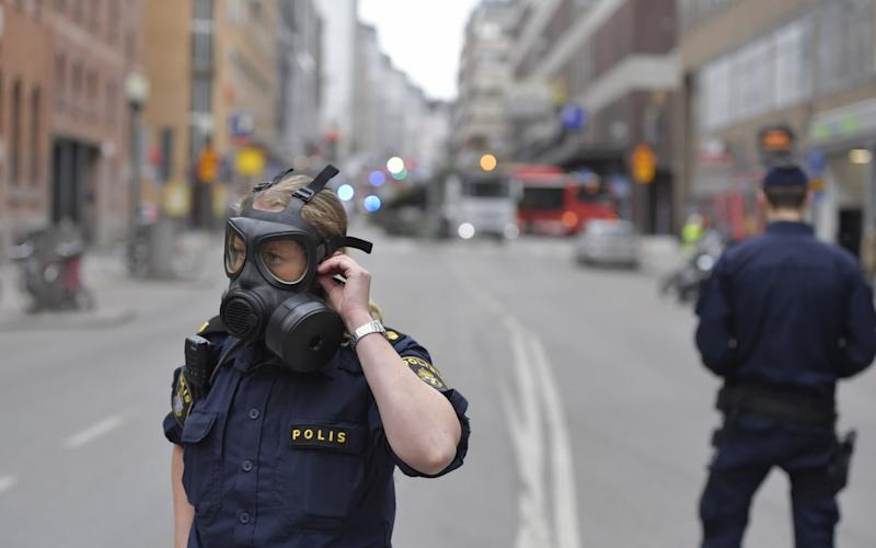 A police officer in a gas mask - Credit: Jessica Gow/TT NEWS AGENCY